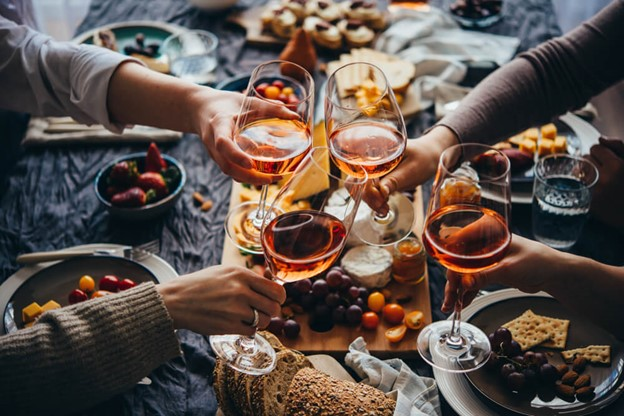 Hands toasting with wine glasses over cheese board