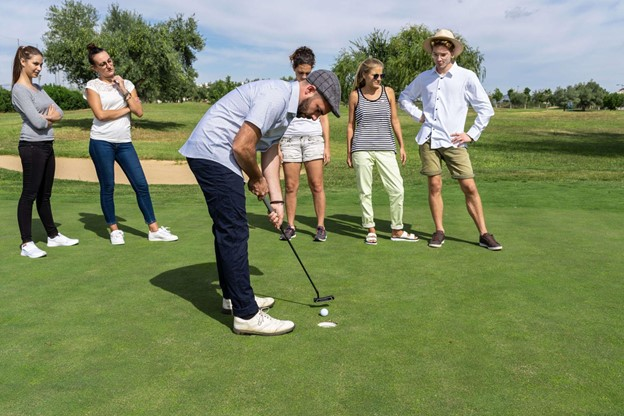 man putting a golf ball on green while friends watch